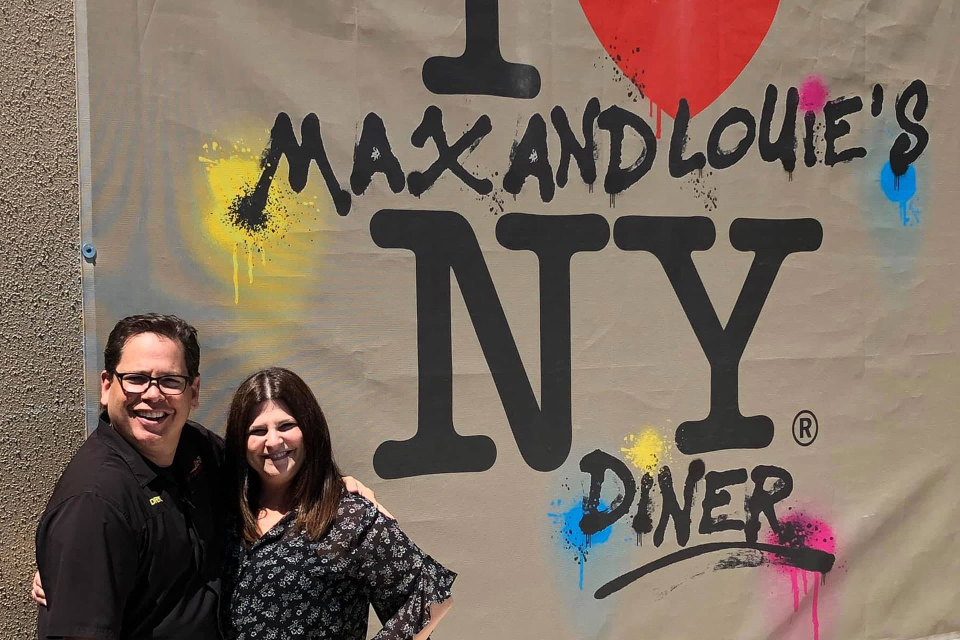 Owners of Max and Louie's New York Diner standing in front of graffiti signage