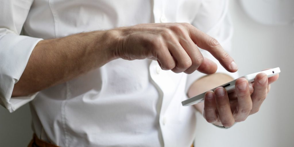 Businessman using digital marketing tools from his phone.